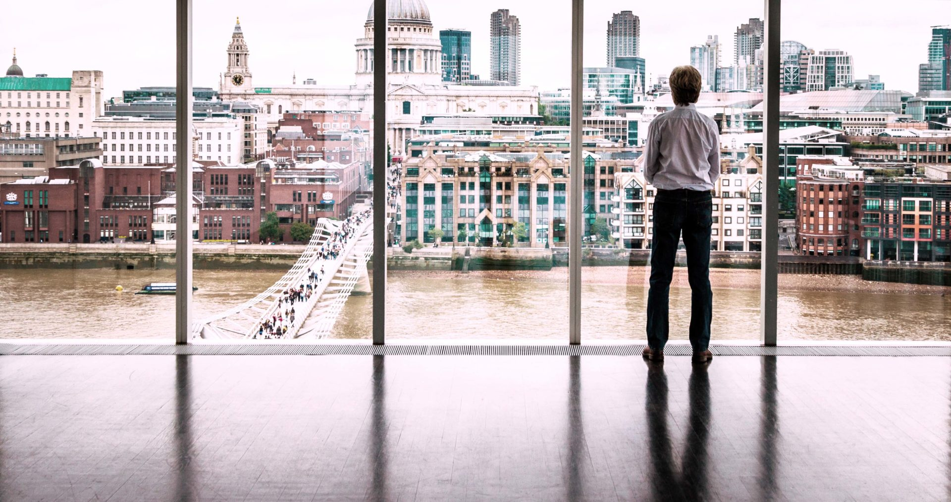 Rear view image of a businessman looking out at the modern London skyline from high up in his office building. He is looking across the river Thames, across the Millennium Bridge to St Paul's cathedral and the high rise skyscrapers of the City of London. He has his hands folden in front of him. Horizontal colour image with copy space.