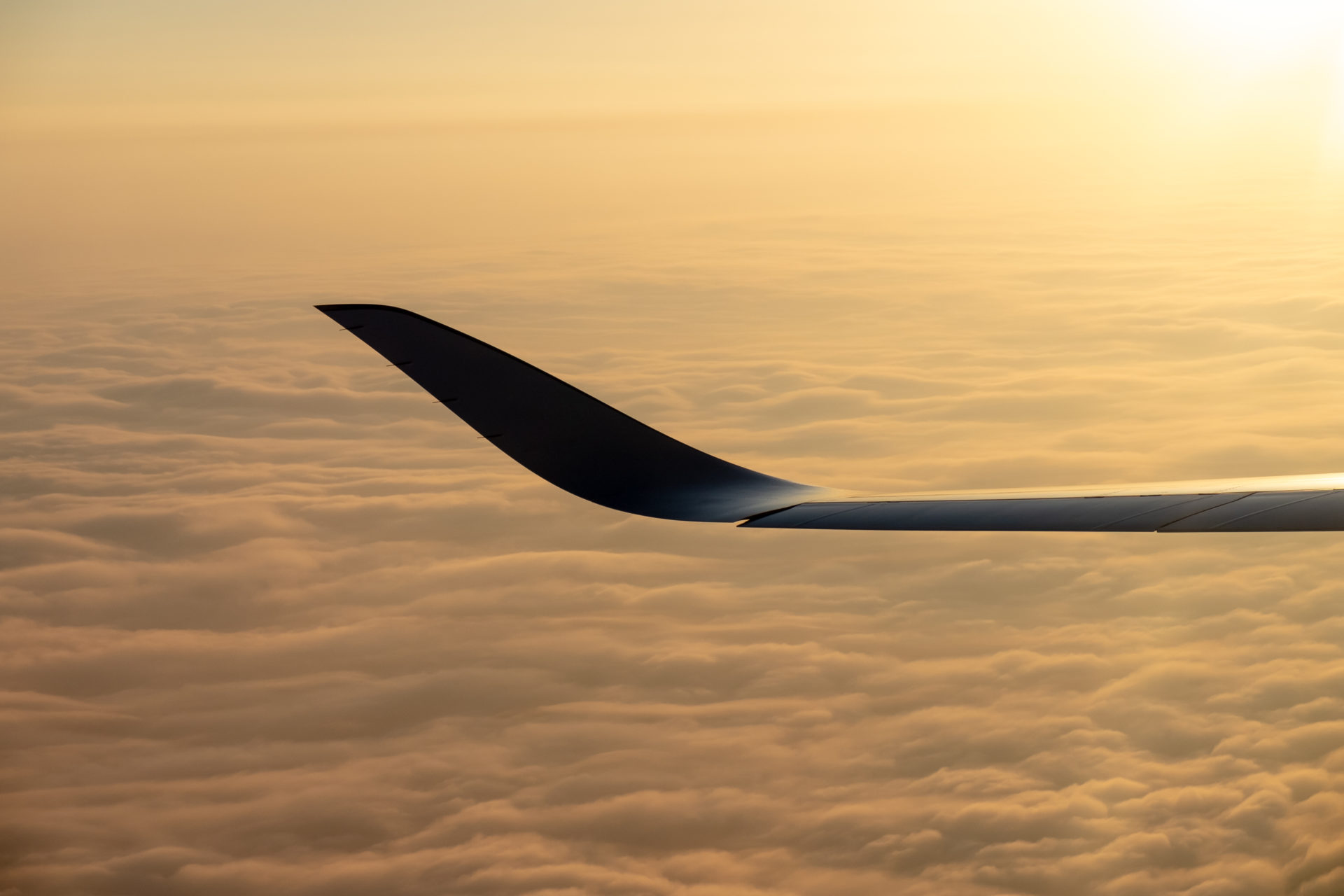 Airplane winglet over cloud carpet at sunset