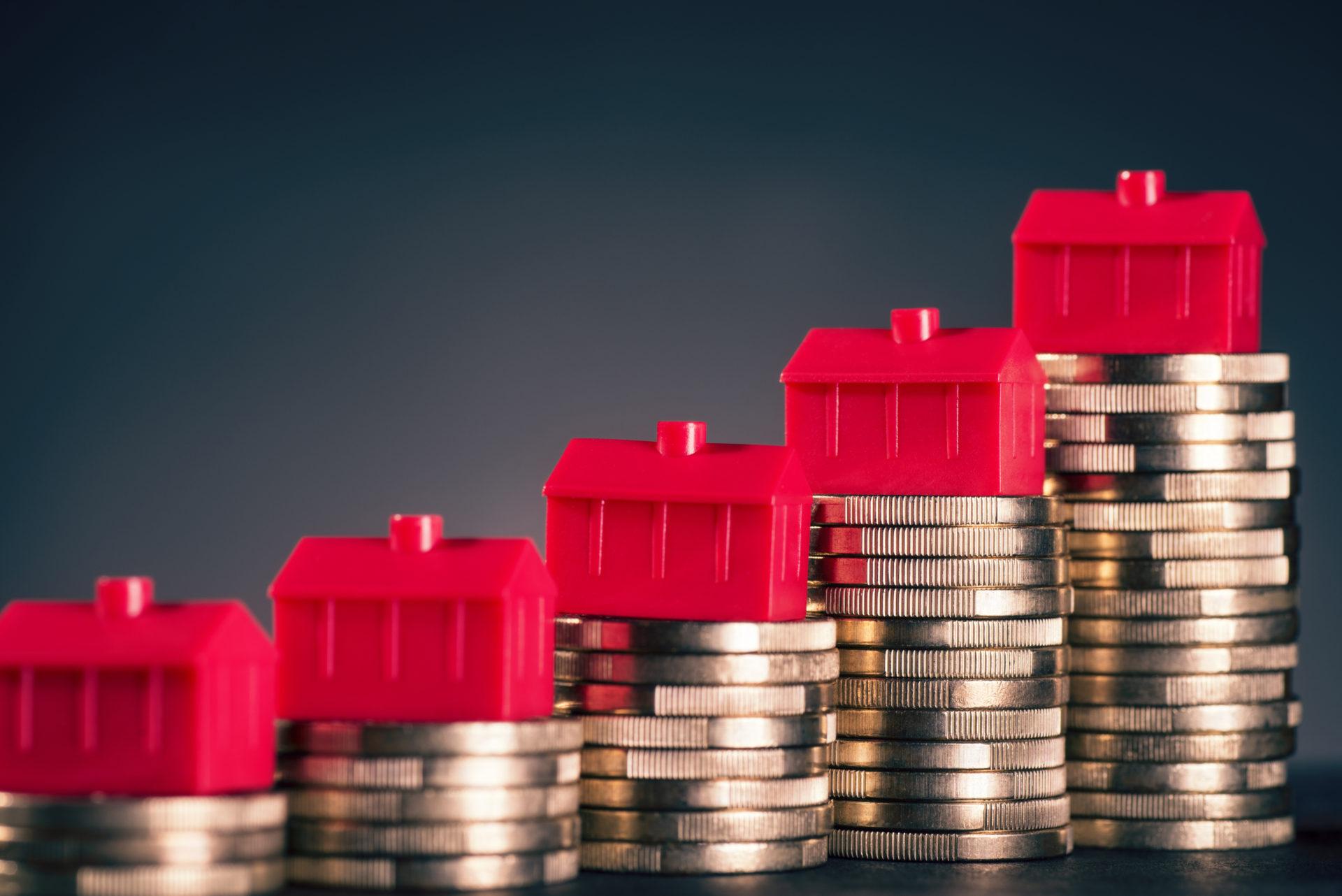Les petites maisons rouges se tiennent sur des piles avec des pièces de monnaie.