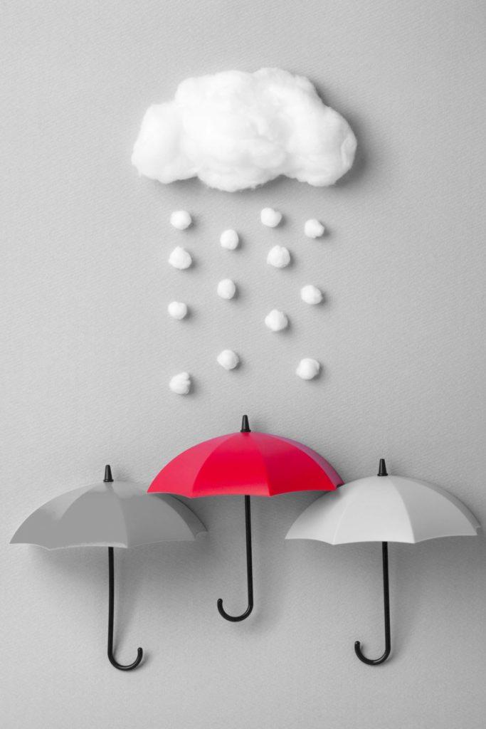 Three umbrellas under the cloud on sky blue background.